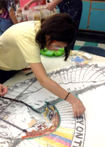Student pieces tiles onto the mural