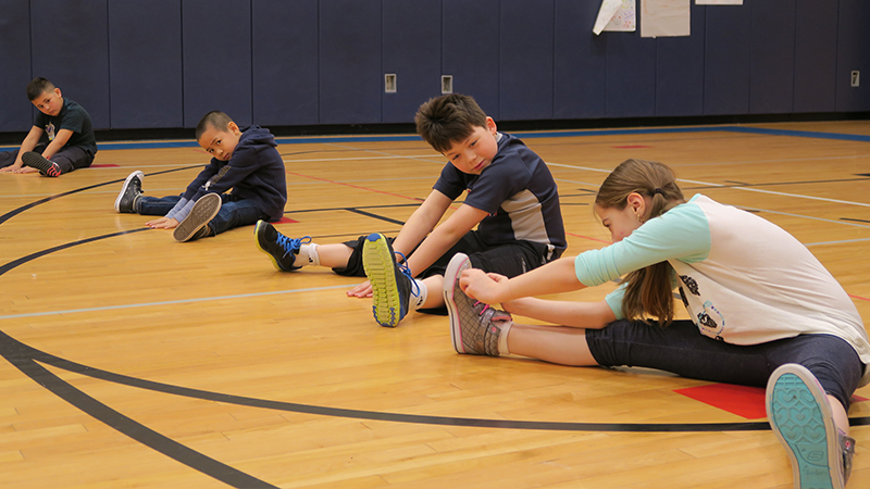 Students stretch during PE Class