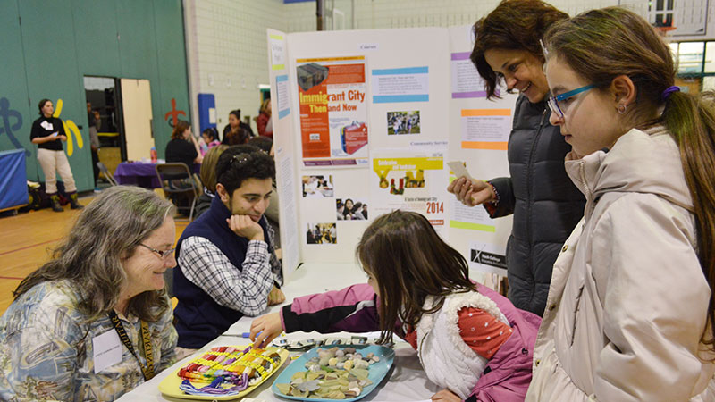 Families visiting a booth at the Summer Activities Fair