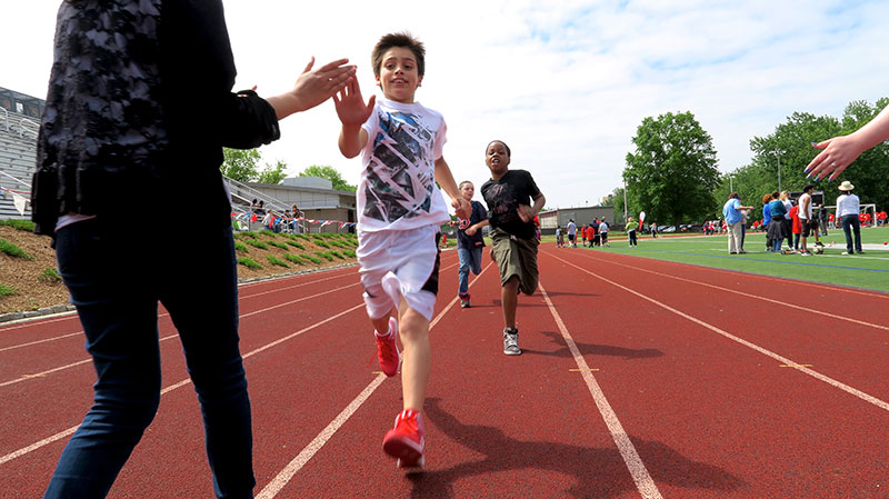 Student crosses finish line during Special Olympics