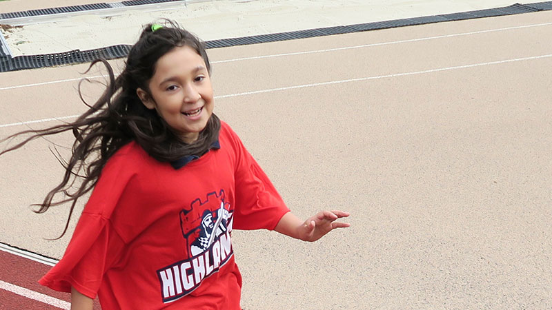 Girl running on track during Somerville Special Olympics