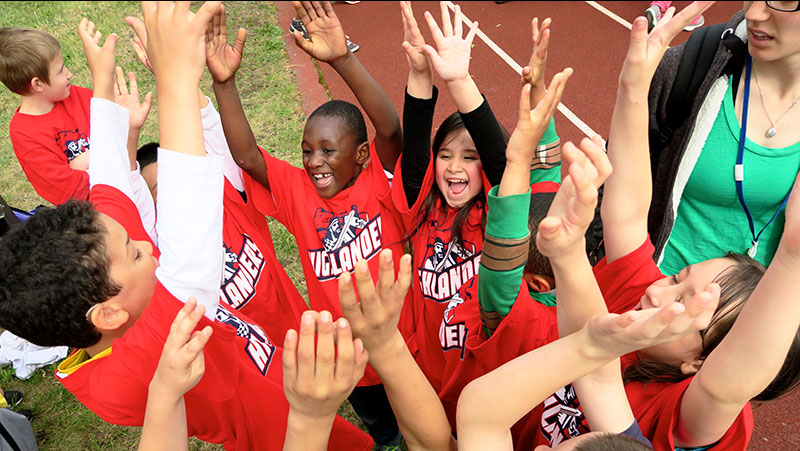 Students celebrate with hands in the air during Somerville Special Olympics